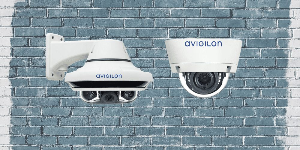 Avigilon indoor and outdoor dome cameras against a brick backdrop