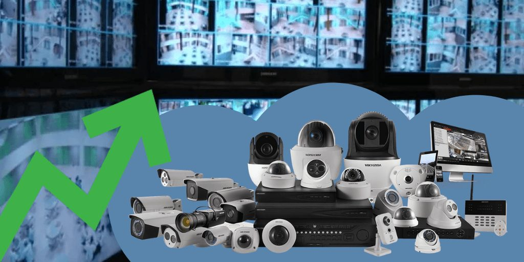 A video surveillance room filled with video security system cameras and equipment and an arrow showing an upward trend