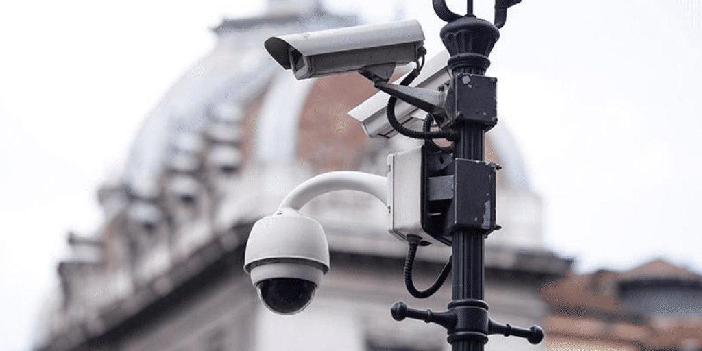 An assortment of video surveillance cameras mounted on light post net to a building