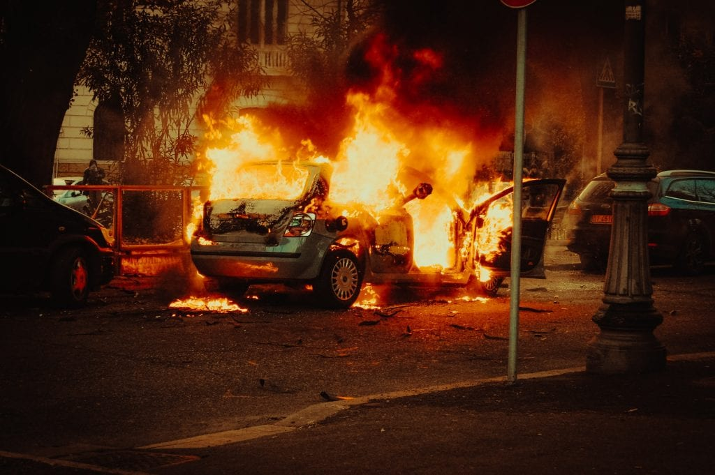 A burning car parked in the street at night resulting in costly property crime
