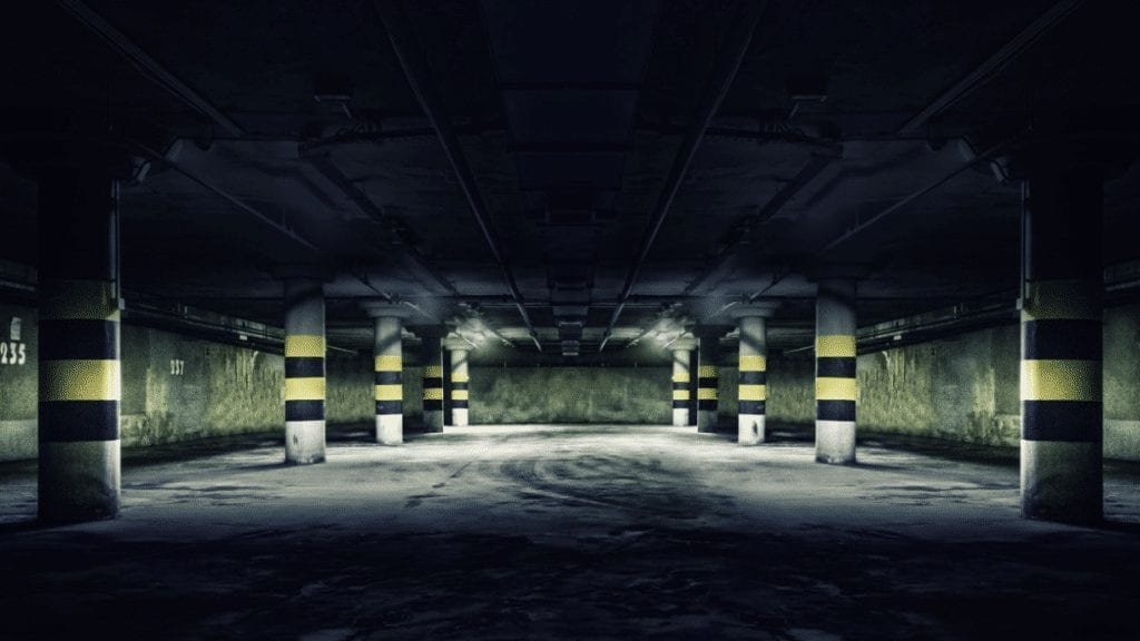 A dark underground parking lot structure with minimal lighting and no video camera surveillance.