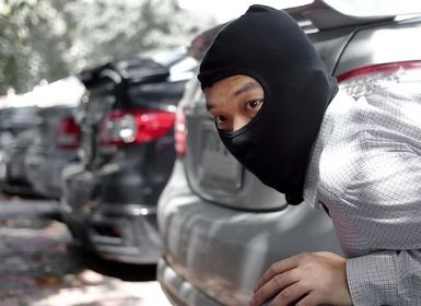 A man in a black ski masks crouched and hiding behind a vehicle